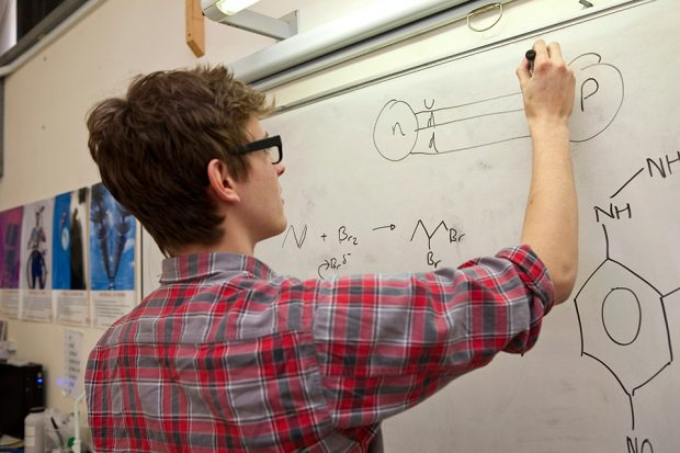 A student drawing chemical notations on a whiteboard