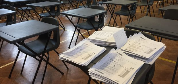 Four piles of exam papers on a desk in an empty exam hall