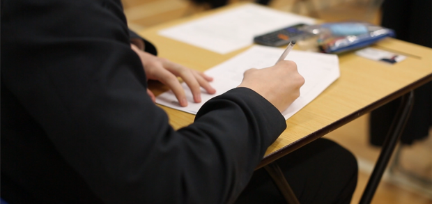 A student at a desk writing on an exam paper.