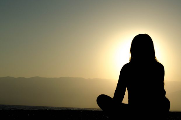 Photo of sunset with rear-view silhouette of woman sitting cross-legged in bottom right corner