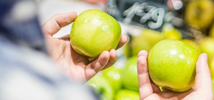 A person holding an apple in each hand